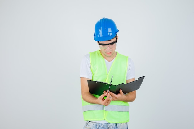 Jeune garçon lisant des notes dans le presse-papiers en uniforme de construction et à la vue de face, focalisée.