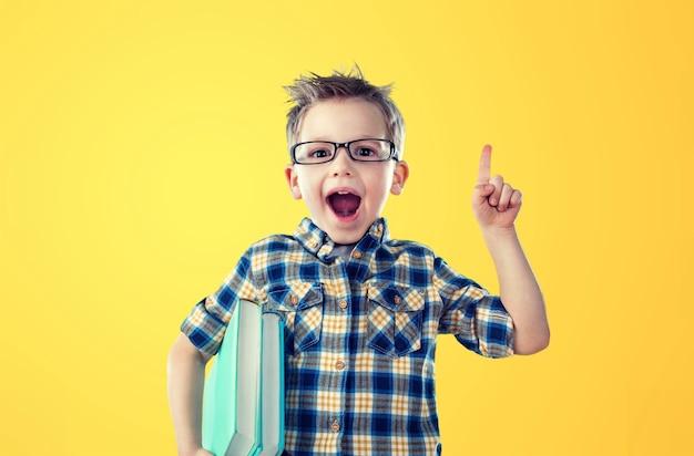 Jeune garçon avec livre sur fond jaune