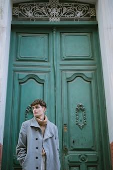Jeune garçon avec manteau à la porte d'entrée
