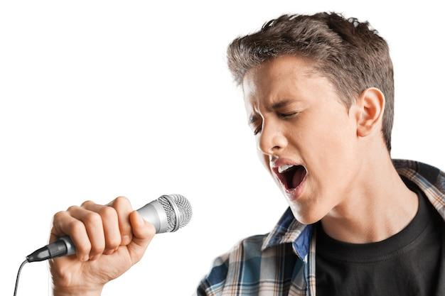 Jeune garçon avec microphone sur fond blanc
