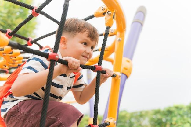 Jeune garçon monte sur la clôture de la corde noire et la barre jaune de sa main pour faire de l'exercice dans une aire de jeux extérieure sous le grand arbre. photos de style effet effet vintage.