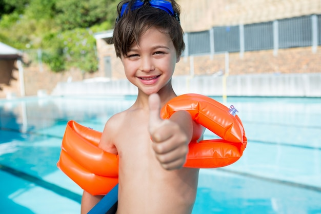 Jeune garçon montrant les pouces vers le haut au bord de la piscine