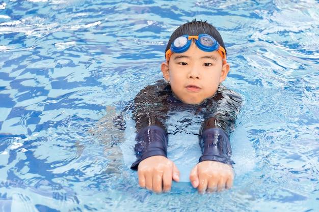 Jeune garçon nageant dans la piscine.