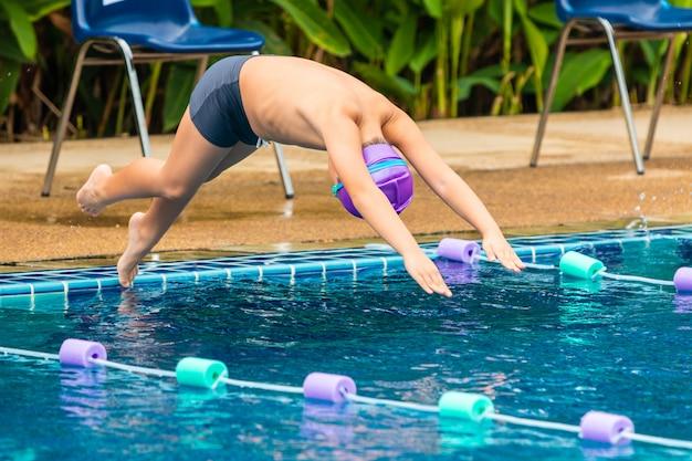Jeune garçon nageur plongeant à la piscine