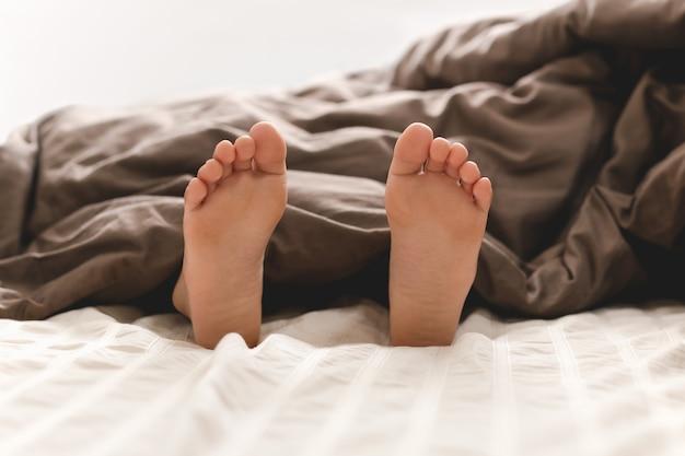 Jeune garçon, pieds nus, dans lit