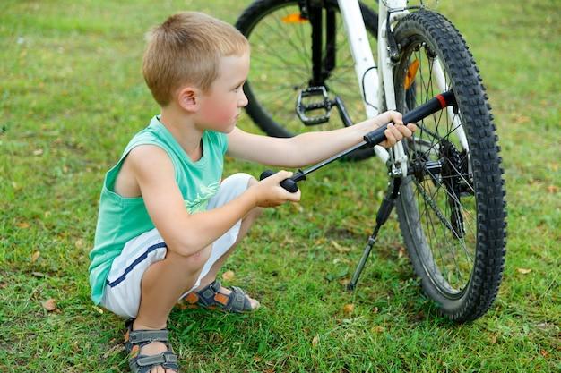 Jeune garçon pompant le tube de vélo