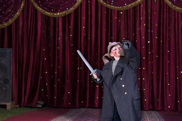 Jeune garçon portant un maquillage de clown et un manteau de taille supérieure tenant une épée de jouet avec le bras levé debout sur scène avec un rideau rouge