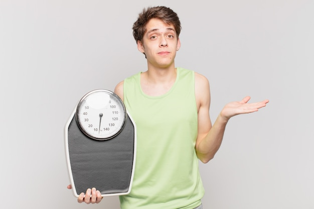 Jeune garçon portant des vêtements de fitness avec un concept d'échelle de poids
