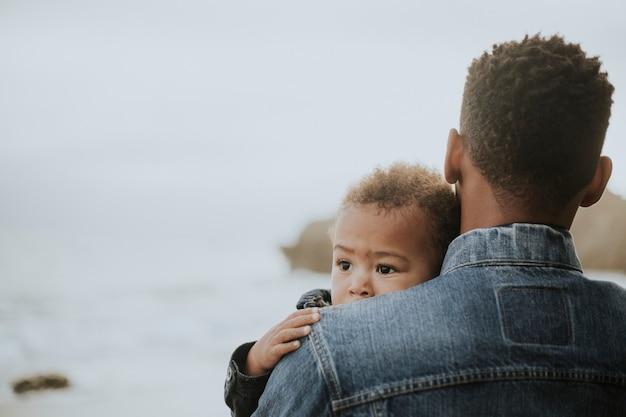 Jeune garçon porté par son père en plein air