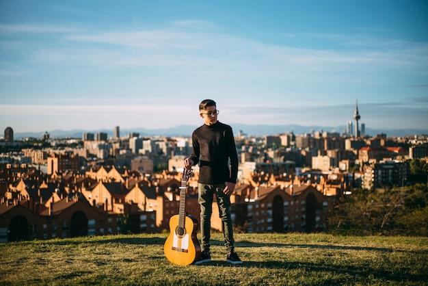 Jeune garçon posant avec guitare dans la ville de madrid, espagne.