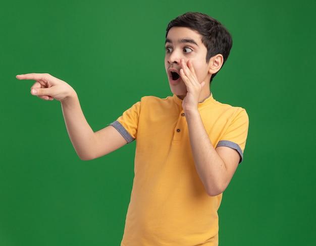Jeune garçon de race blanche impressionné en gardant la main près de la bouche à la recherche et en pointant sur le côté en chuchotant