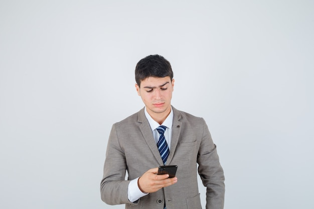 Jeune garçon regardant le téléphone en costume formel et à la recherche concentrée. vue de face.