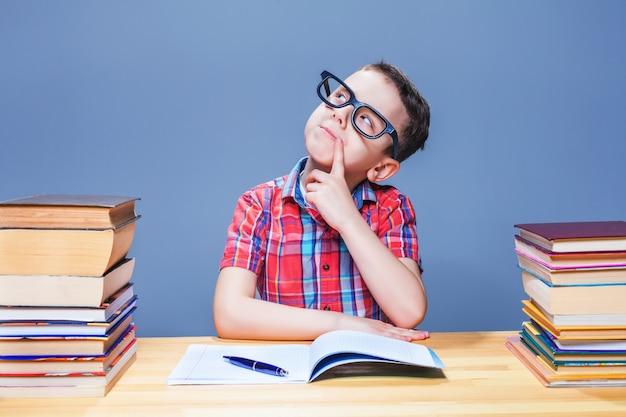 Jeune garçon rêve au bureau de la bibliothèque de l'école. écolier à lunettes contre de nombreux livres. petit concept d'élève
