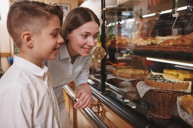 Jeune garçon et sa belle mère choisissant des desserts à acheter à la boulangerie locale