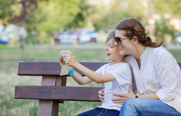 Jeune garçon et sa mère à l'aide de smartphone pour prendre selfie. passer un appel vidéo. appel vidéo en ligne en streaming. internet mobile.