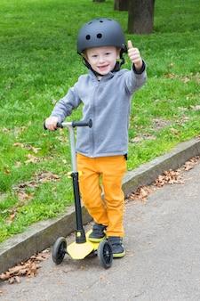 Jeune garçon avec scooter jaune sur le parc