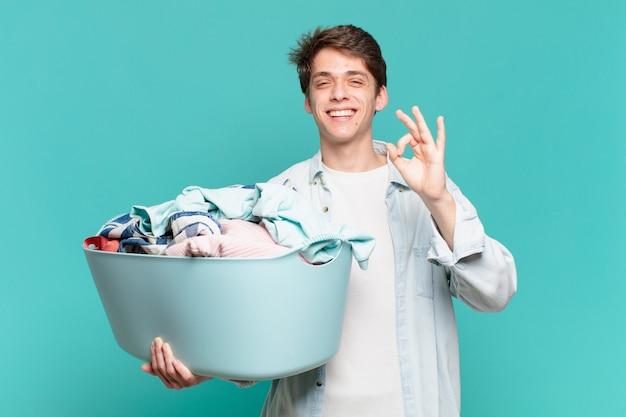 Jeune garçon se sentant heureux, détendu et satisfait, montrant son approbation avec un geste correct, souriant concept de lavage de vêtements