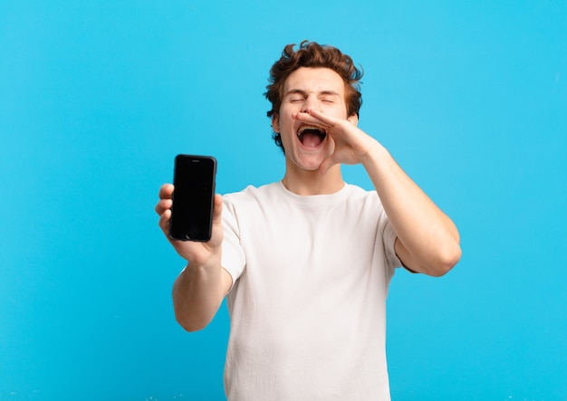 Jeune garçon se sentant heureux, excité et positif, donnant un grand cri avec les mains à côté de la bouche, appelant. concept d'écran de téléphone