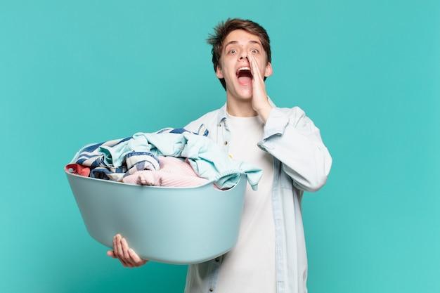 Jeune garçon se sentant heureux, excité et positif, donnant un grand cri avec les mains à côté de la bouche, appelant le concept de lavage de vêtements