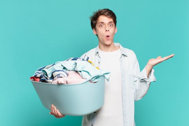Jeune garçon semblant surpris et choqué, avec la mâchoire tombée tenant un objet avec une main ouverte sur le côté, concept de lavage de vêtements