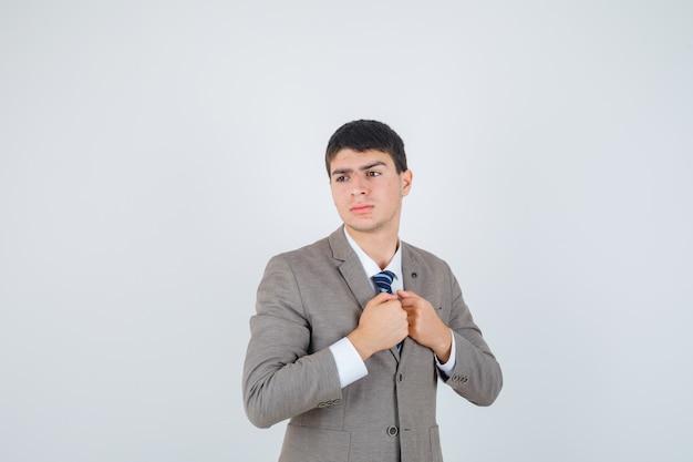 Jeune garçon serrant les poings sur la poitrine, détournant les yeux en costume formel et à la pensif. vue de face.