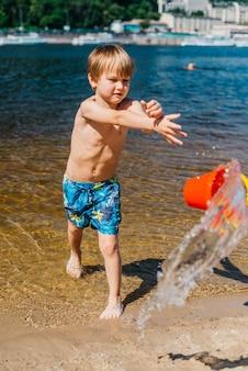 Jeune garçon en short jetant un seau d'eau sur la plage de la mer