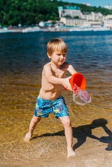 Jeune garçon en short verser de l'eau sur la plage de la mer