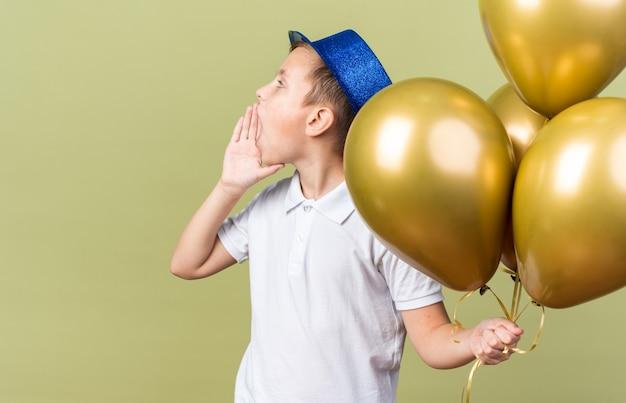 Jeune garçon slave avec un chapeau de fête bleu tenant des ballons à l'hélium et gardant la main près de la bouche appelant quelqu'un regardant le côté isolé sur un mur vert olive avec espace de copie