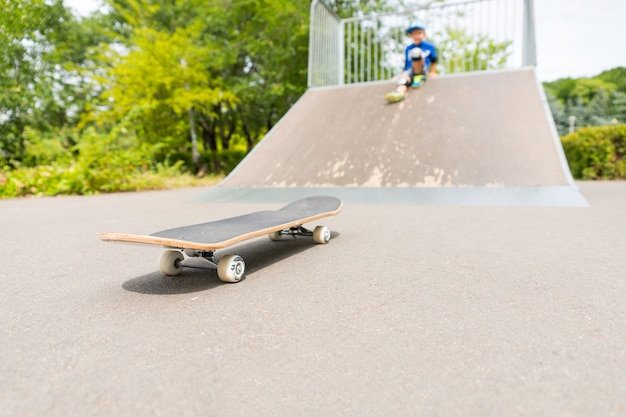 Jeune garçon en soft focus assis sur le dessus de la rampe dans le skate park regardant la planche à roulettes au point en bas