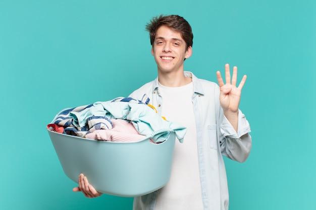 Jeune garçon souriant et à l'air sympathique, montrant le numéro quatre ou quatrième avec la main vers l'avant, compte à rebours concept de lavage de vêtements