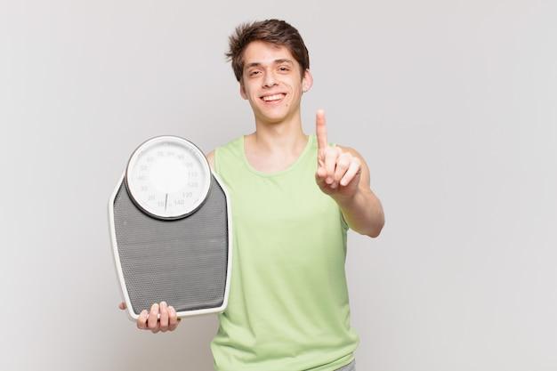 Jeune garçon souriant fièrement et avec confiance faisant la pose numéro un se sentant triomphalement comme un leader