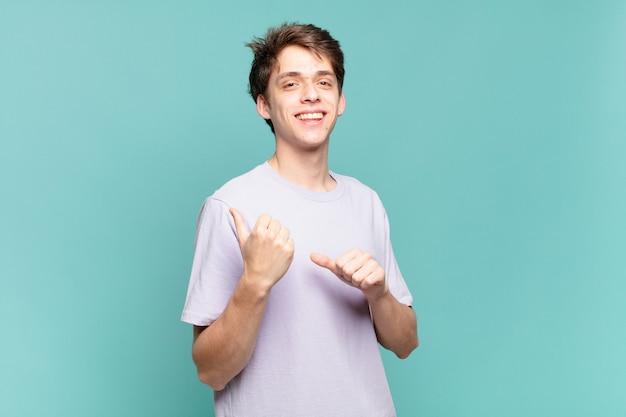 Jeune garçon souriant joyeusement et désinvolte pointant vers l'espace de copie sur le côté, se sentant heureux et satisfait