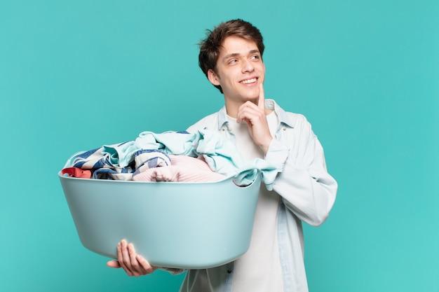 Jeune garçon souriant joyeusement et rêvant ou doutant, regardant sur le côté le concept de lavage de vêtements