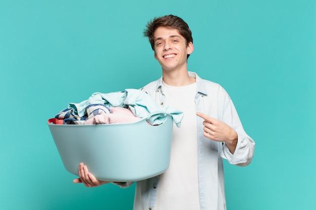 Jeune garçon souriant joyeusement, se sentant heureux et pointant vers le côté et vers le haut, montrant l'objet dans l'espace de copie concept de lavage de vêtements