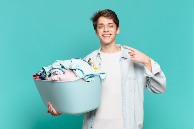 Jeune garçon souriant en toute confiance pointant vers son propre large sourire, attitude positive, détendue et satisfaite, concept de lavage de vêtements