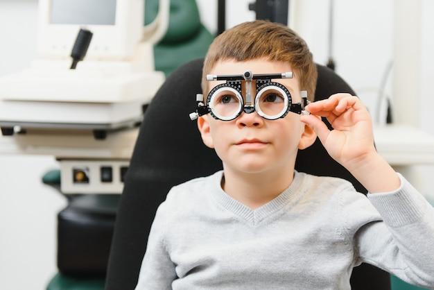 Jeune garçon subissant un examen de la vue avec des lunettes dans une clinique médicale