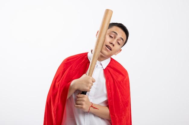Jeune garçon de super-héros en cape rouge se battre au visage avec une batte de baseball avec les yeux fermés isolé sur fond blanc avec copie espace