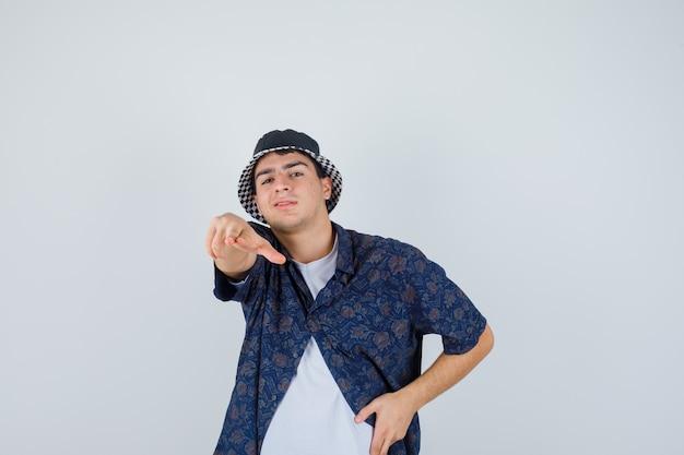 Jeune garçon en t-shirt blanc, chemise à fleurs, casquette montrant le geste du pistolet vers la caméra, tenant la main sur la taille et l'air heureux, vue de face.