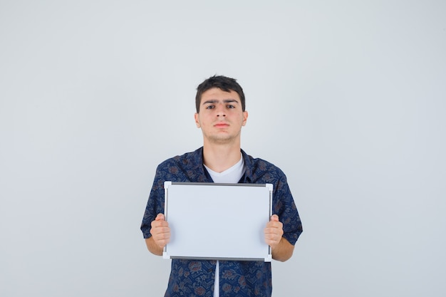 Jeune garçon en t-shirt blanc, chemise à fleurs tenant un tableau blanc et ayant l'air confiant