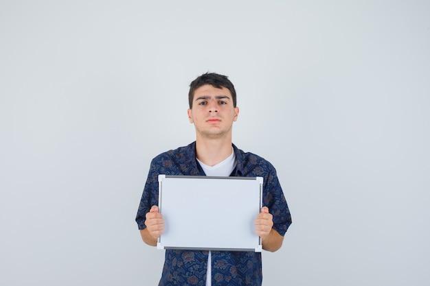 Jeune garçon en t-shirt blanc, chemise à fleurs tenant un tableau blanc et à la vue de face, confiant.
