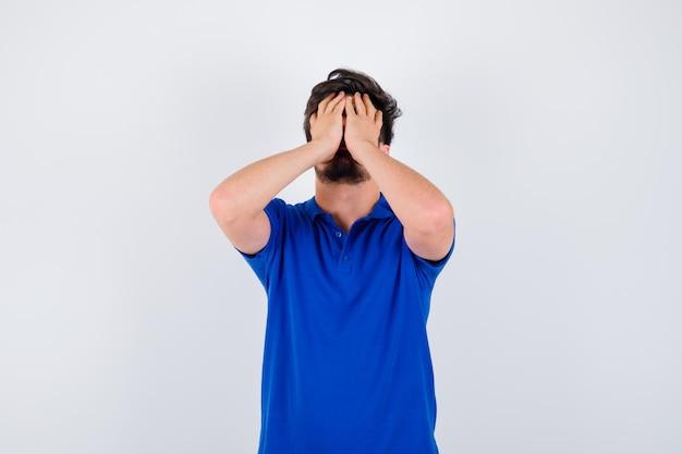 Jeune garçon en t-shirt bleu couvrant une partie du visage avec la main et l'air ennuyé, vue de face.