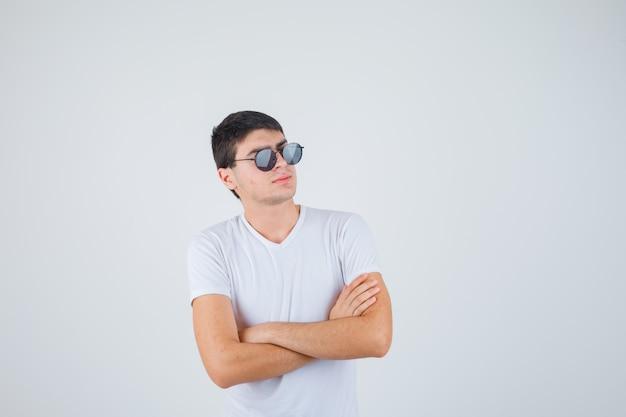 Jeune garçon en t-shirt debout avec les bras croisés et à la confiance en soi, vue de face.