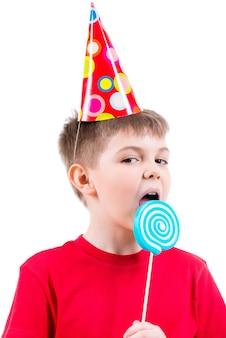 Jeune garçon en t-shirt rouge et chapeau de fête de manger des bonbons colorés - isolé sur blanc