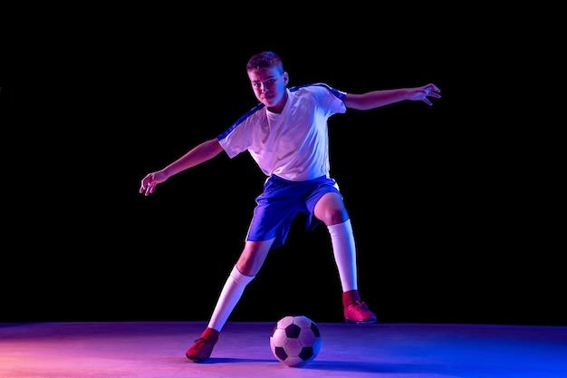Jeune garçon en tant que joueur de football ou de football sur un mur sombre