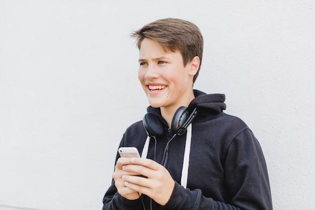 Jeune garçon avec téléphone sur la rue