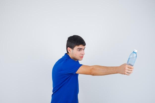 Jeune garçon tenant une bouteille d'eau, le donnant à quelqu'un en t-shirt bleu et l'air heureux. vue de face.