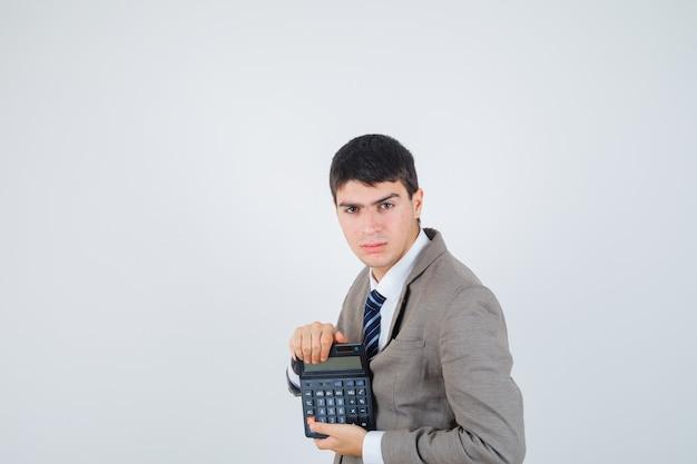 Jeune garçon tenant la calculatrice en costume formel et à la vue de face, confiant.