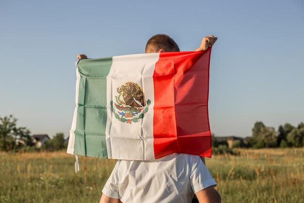 Jeune garçon tenant le drapeau du mexique.