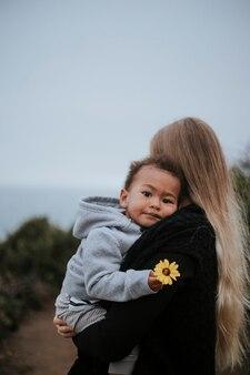 Jeune garçon tenant une fleur portée par sa maman