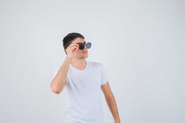 Jeune garçon tenant des lunettes, regardant de côté en t-shirt et à la cool, vue de face.
